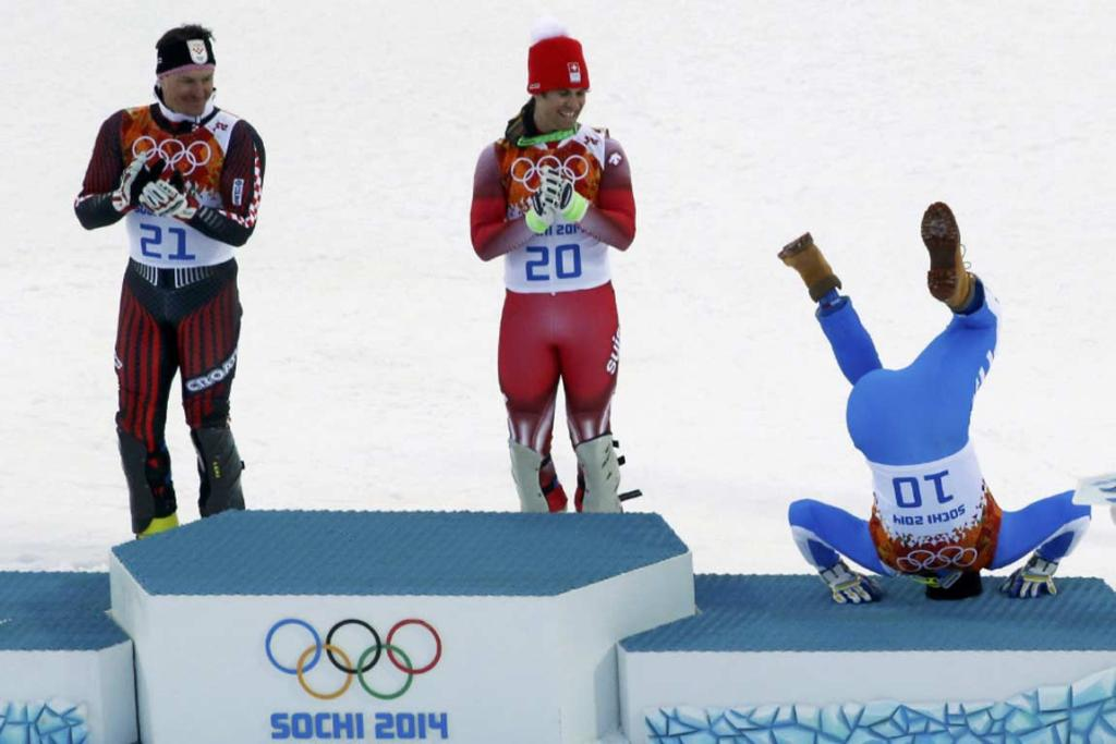Bronze medalist Christof Innerhofer of Italy does a forward roll to get on the men's super combined podium.