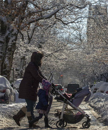 STORM BLOWS OVER: A woman crosses the street with children through slush and snow in the Park Slope section of Brooklyn, New York.