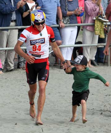 SHARING THE MOMENT: Coast to Coast winner Braden Currie heads to the finish line at Sumner Beach with his five-year-old son Tarn.
