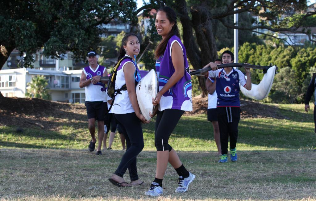 Stevie Pomare (front) and Autumn Pomare (left) from team Portage Crossing take their waka to the water.