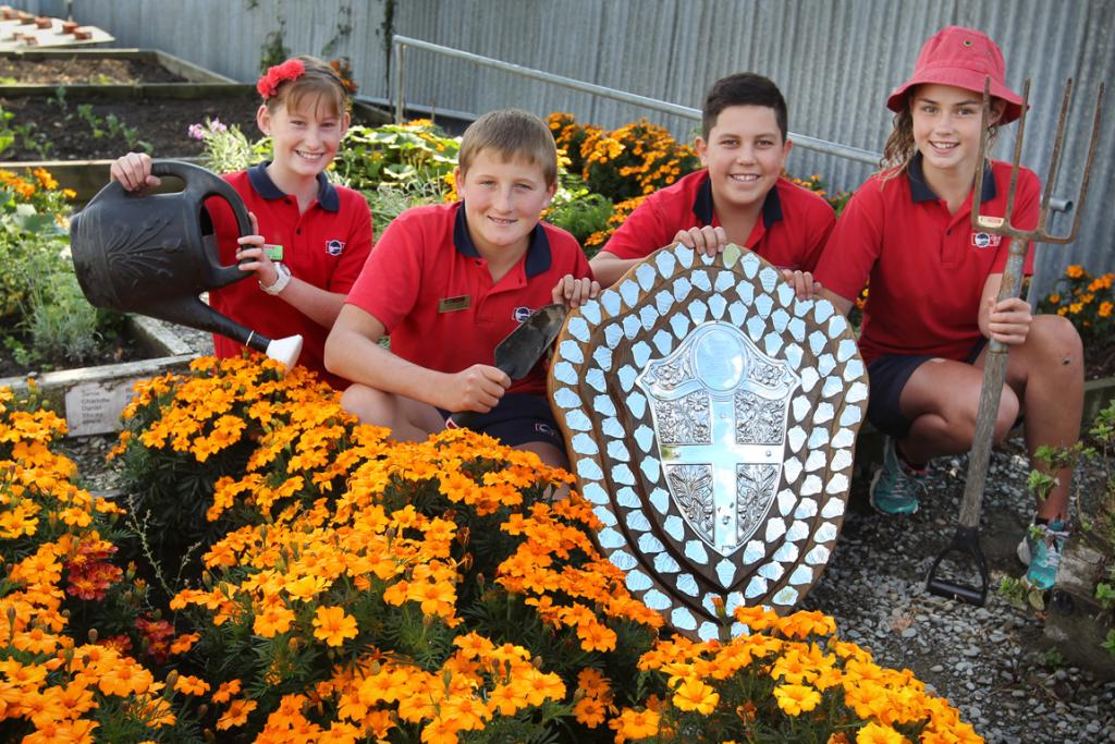 Isellah Gordon, from left, Jellicoe house leader, Lleyton Phillips, school leader, Ryan Brosnahan, Evans house leader and Angel Small, school leader, with the Hurdley Shield in the school garden.
