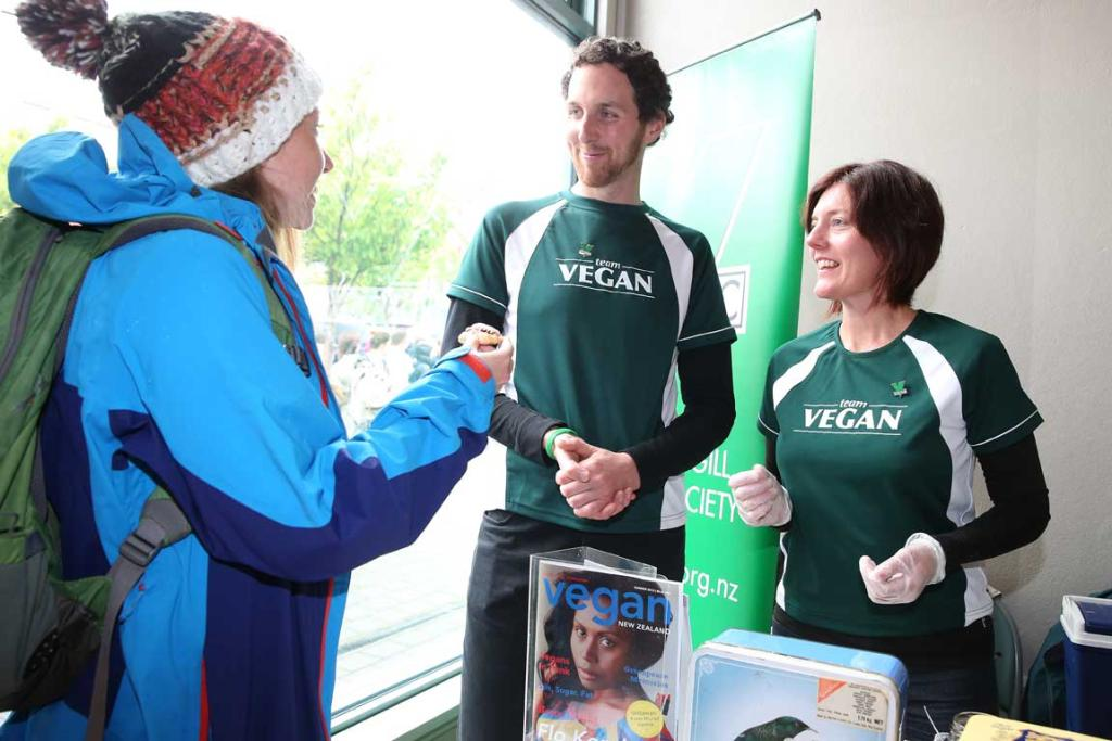 Student Steph Grange gets a pikelet from Jordan Wyatt and Jenny Stone, of the Invercargill Vegan Society at SIT during day one of this year's O Week.