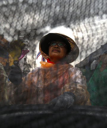 An anti-government protester sits behind a barricade near Government Complex in Bangkok.