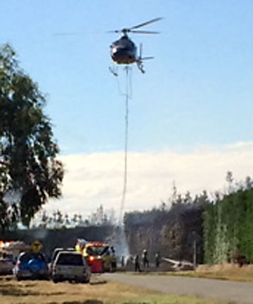 AERIAL ATTACK: A helicopter was brought in to douse the flames.