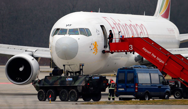 AFTER THE FACT: A police vehicle guards in front of the hijacked Ethiopian Airlines flight ET 702 after passengers disembarked at Cointrin Airport in Geneva. Social media users were onto the hijacking before media reported it.