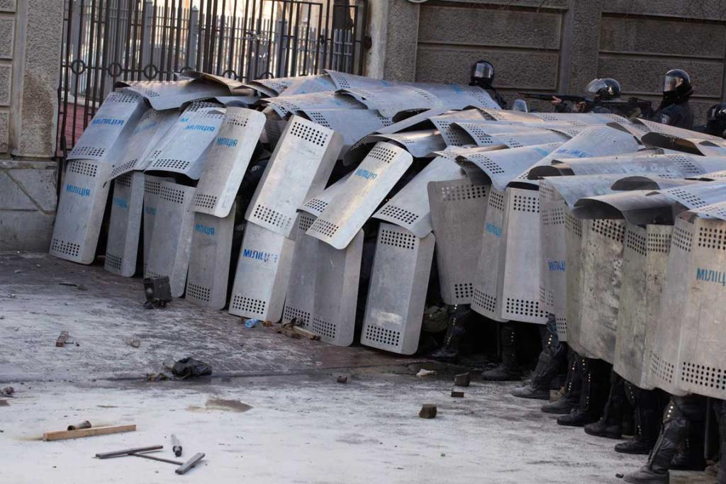 Interior Ministry members take cover behind shields during clashes with anti-government protesters.