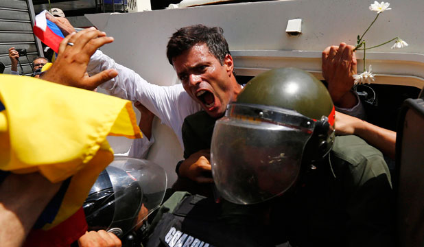 Venezuelan opposition leader Leopoldo Lopez pumps his fist as he gets into a National Guard armoured vehicle after surrendering to authorities.