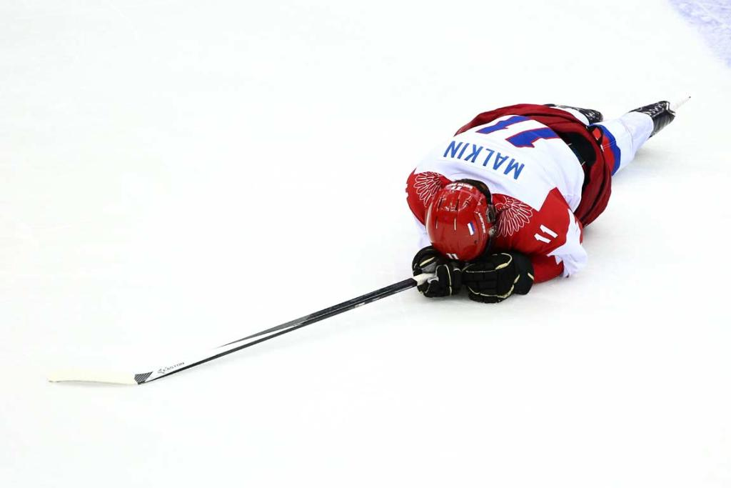 Yevgeni Malkin lies on the ice after being hit in the face by a stick during Russia's 3-1 loss to Finland in the men's ice hockey quarterfinals.