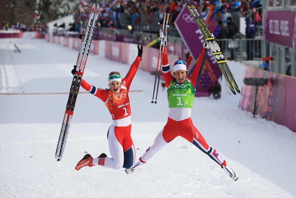 Gold medalists Ingvild Flugstad Oestberg and Marit Bjoergen of Norway leap for the cameras after being part of the winning Norwegian team in the women's team sprint classic.