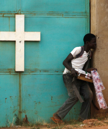 A street vendor hides from gunfire near a church during a firefight in Bangui Tuesday.
