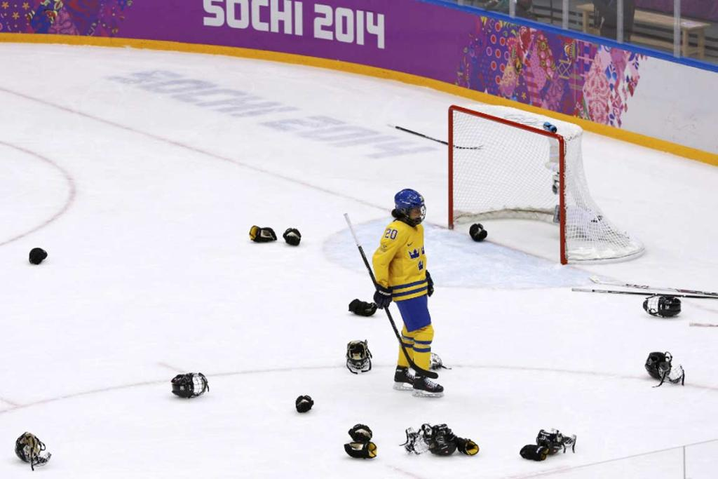 Sweden's Fanny Rask skates between gloves, masks and sticks discarded by the victorious Swiss team.