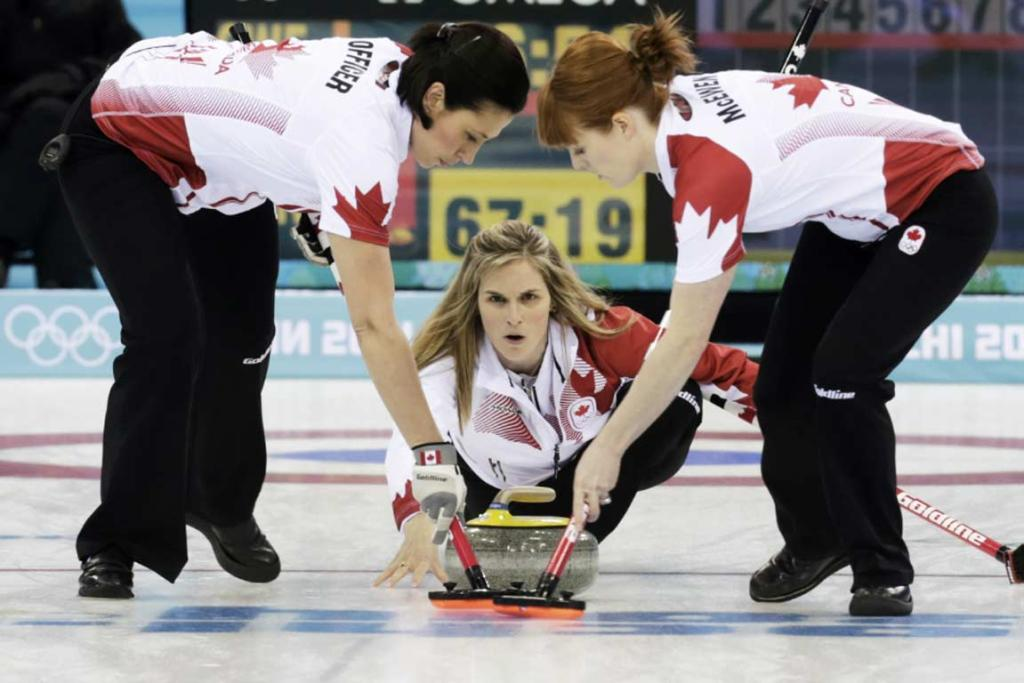 Canada's second Jill Officer (left) and lead Dawn McEwen (right) prepare to sweep as skip Jennifer Jones delivers a stone in their women's gold medal curling game against Sweden.