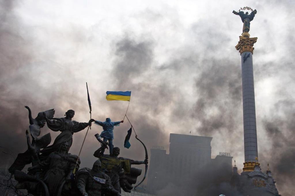 An anti-government protester waves the national flag from the top of a statue in Independence Square, Kiev.