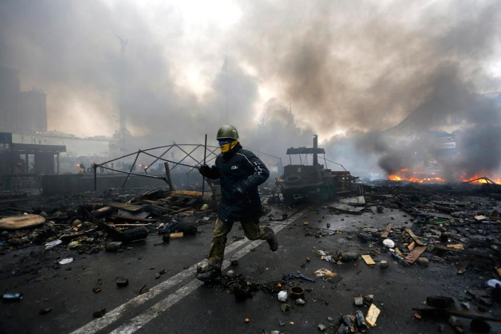 An anti-government protester runs trough the rubble in Independence Square, Kiev.