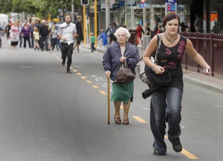 ON THE MOVE: An elderly woman among others fleeing collapsed buildings in central Christchurch after the 6.3 earthquake.