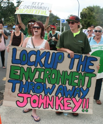 Angry protesters march down The Esplanade at Whitianga