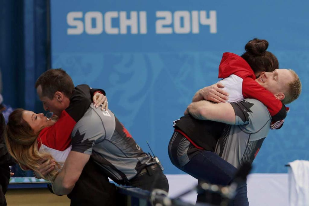Canada's second EJ Harnden (left) hugs wife Rachelle as skip Brad Jacobs hugs wife Shawna after winning men's curling gold.