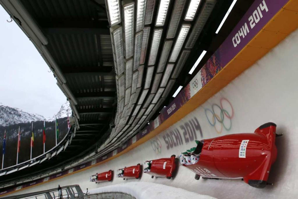 Pilot Simone Bertazzo of Italy speeds down the track during a four-man bobsleigh training run at the Sanki sliding centre in this multiple exposure image.