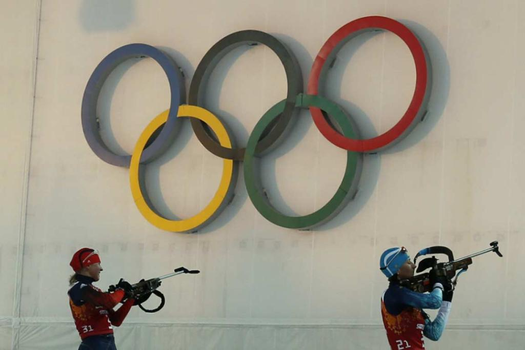 Russia's Yana Romanova prepares to shoot next to Vita Semerenko (right) during the women's biathlon 4x6 km relay event.
