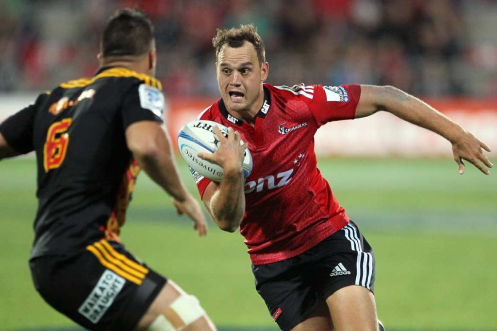 Crusaders fullback Israel Dagg runs at Liam Messam during the season opener.