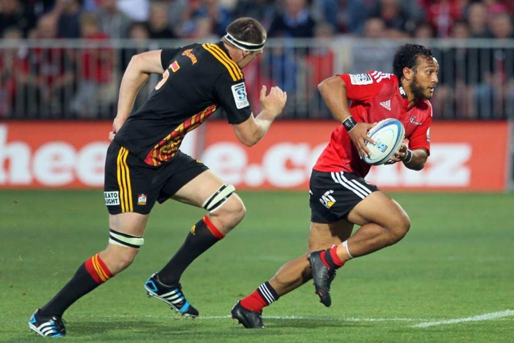 Crusaders wing Nafi Tuitavake runs away from Chiefs lock Brodie Retallick.