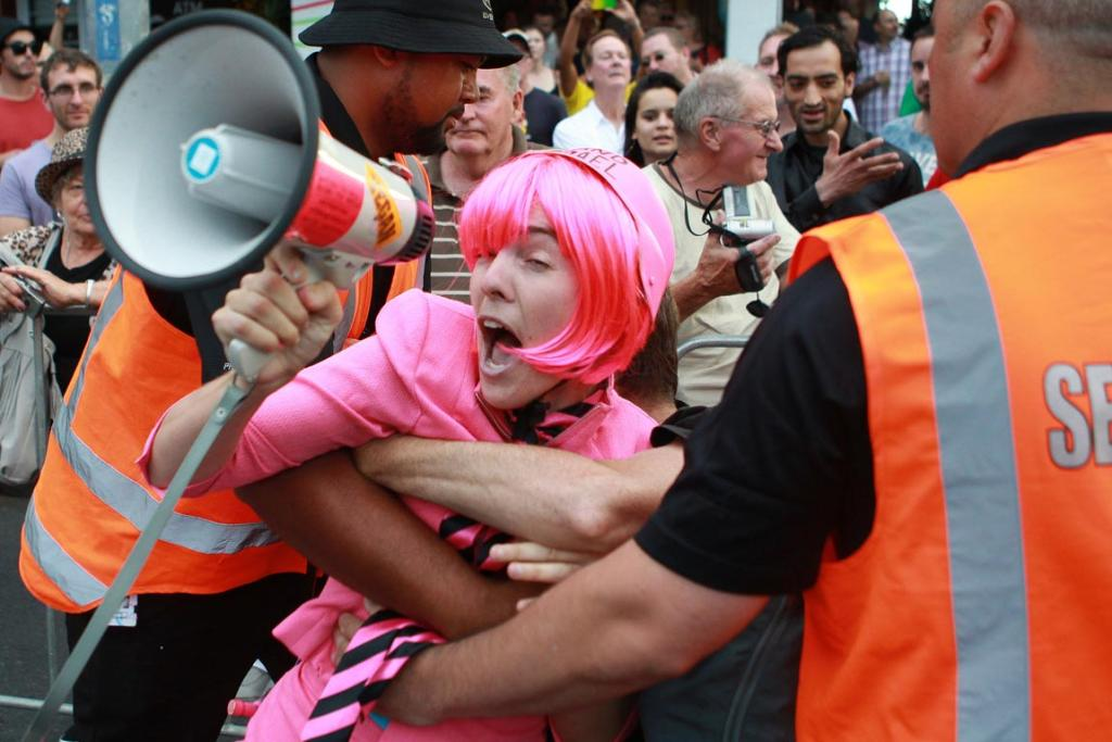 A protester, demonstrating against the Israeli Embassy's presence at the Parade, is removed by security.