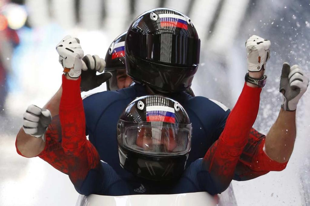 Russian pilot Alexander Zubkov and team-mate Alexey Negodaylo raise their arms triumphantly after winning the four-man bobsled gold at the Sanki Sliding Centre.