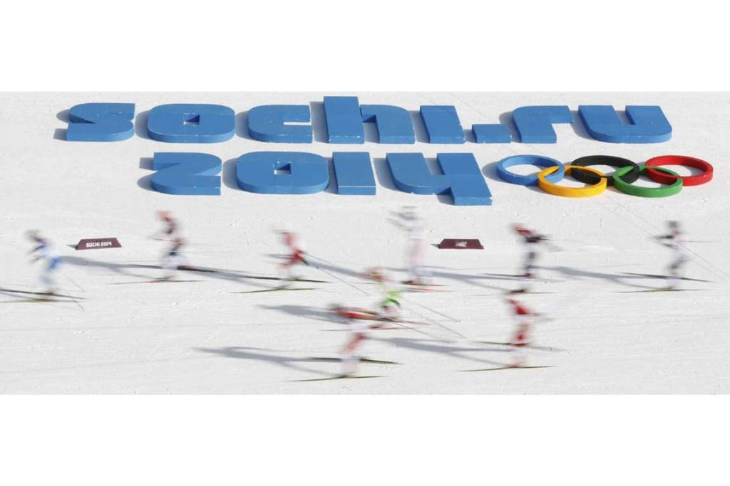 Competitors in the men's 50km mass start cross-country race head past a giant sign for the Sochi Games.