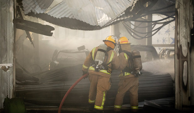 Firefighters walk through a warehouse destroyed by a fire at Te Rapa