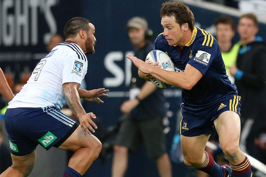 Ben Smith of the Highlanders, right, charges at the Blues' Piri Weepu.