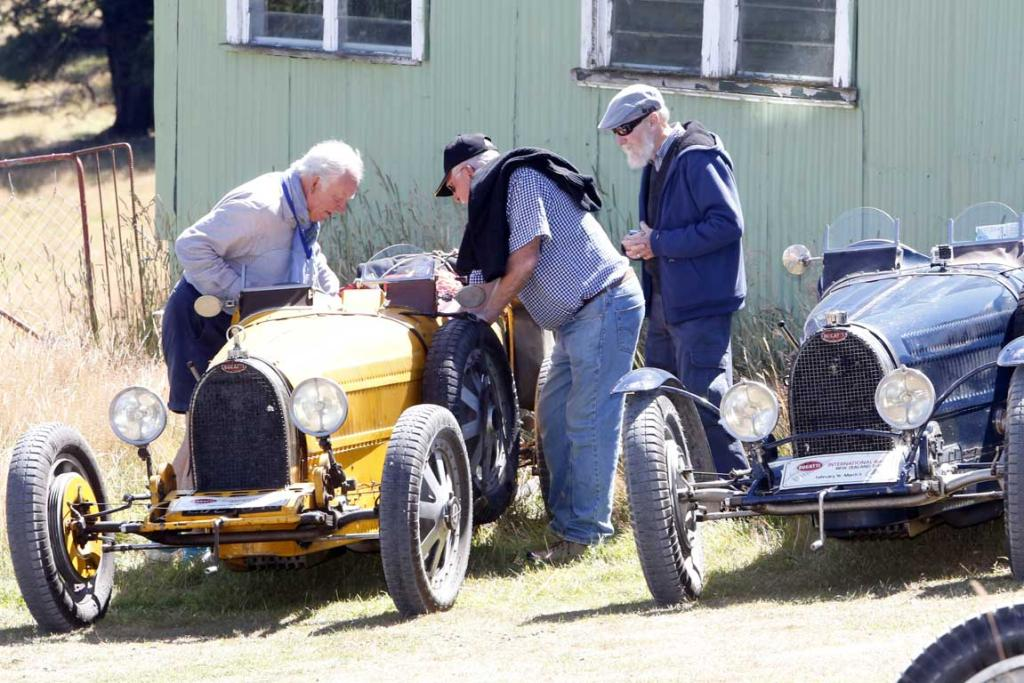 People check out some of the Bugatti vehicles parked at Tophouse Historic Guesthouse in the Nelson region during the Bugatti International Rally in New Zealand.