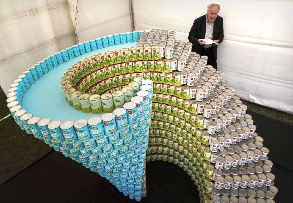 Sir Miles Warren judging an entry in the Canstruction Contest with cans going to the City Mission. On display at the Ellerslie Flower Show in Hagley Park.
