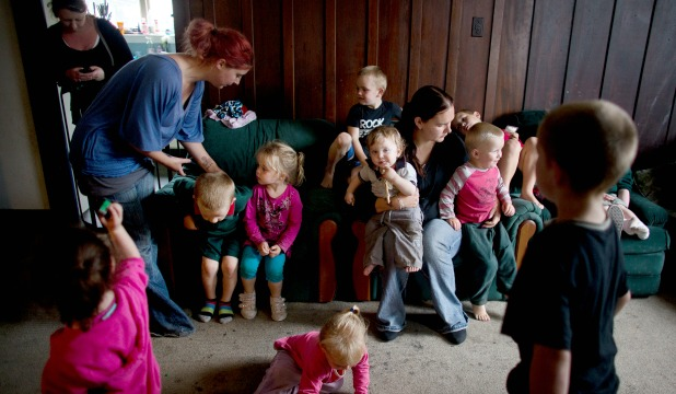 Alysha Ericksen, left, and Adrienne Hiscoke gather together the nine children of a Phillipstown house.