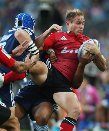 Andy Ellis of the Crusaders is tackled by James Parsons of the Blues tonight in Auckland.