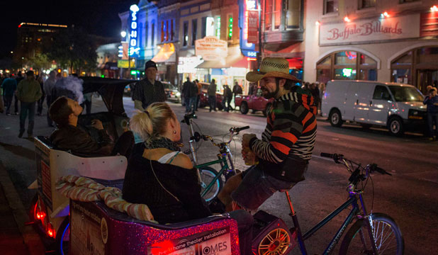 BIG NIGHT OUT: Visitors sit in the back of a tricycle taxi along Sixth Street in Austin, Texas.