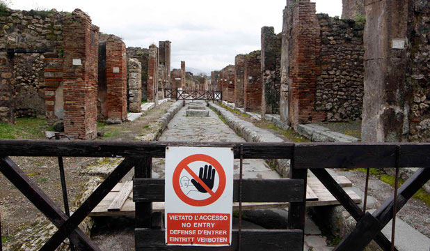 POMPEII FALLING: A sign, which reads: ''No Entry'', hangs on a perimeter fence in the ancient Roman city Pompeii, which was buried in AD 79 by an eruption of the Vesuvius volcano.