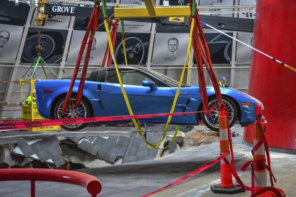 Workers use a crane to recover the first Chevrolet Corvette, the 2009 Corvette ZR-1