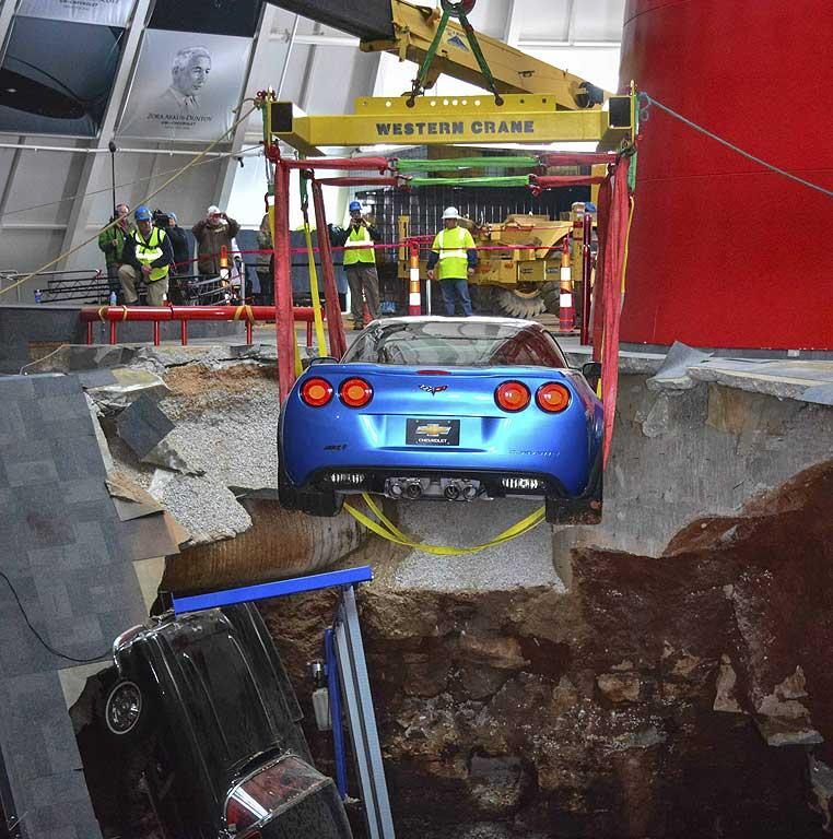 "Workers use a crane to recover the first Chevrolet Corvette, the 2009 Corvette ZR-1 ""Blue Devil,"" from the sinkhole at the National Corvette Museum in Bowling Green, Kentucky."
