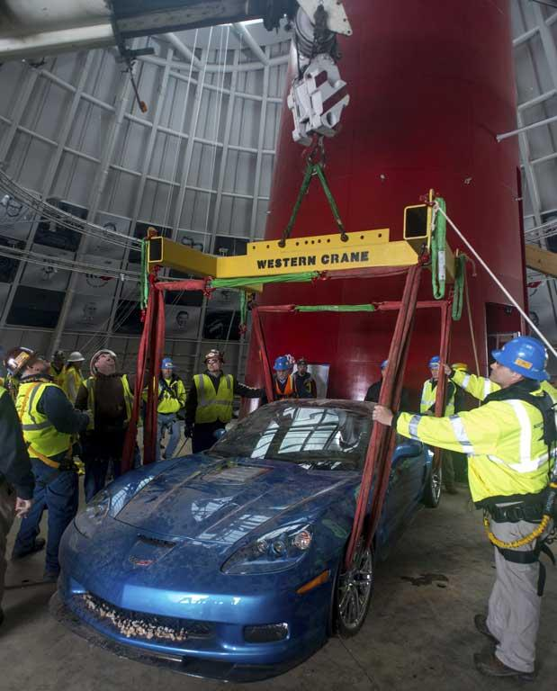 "Workers set the 2009 Chevrolet Corvette ZR-1 ""Blue Devil"" on the ground after using a crane to recover it from the sinkhole at the National Corvette Museum in Bowling Green, Kentucky."