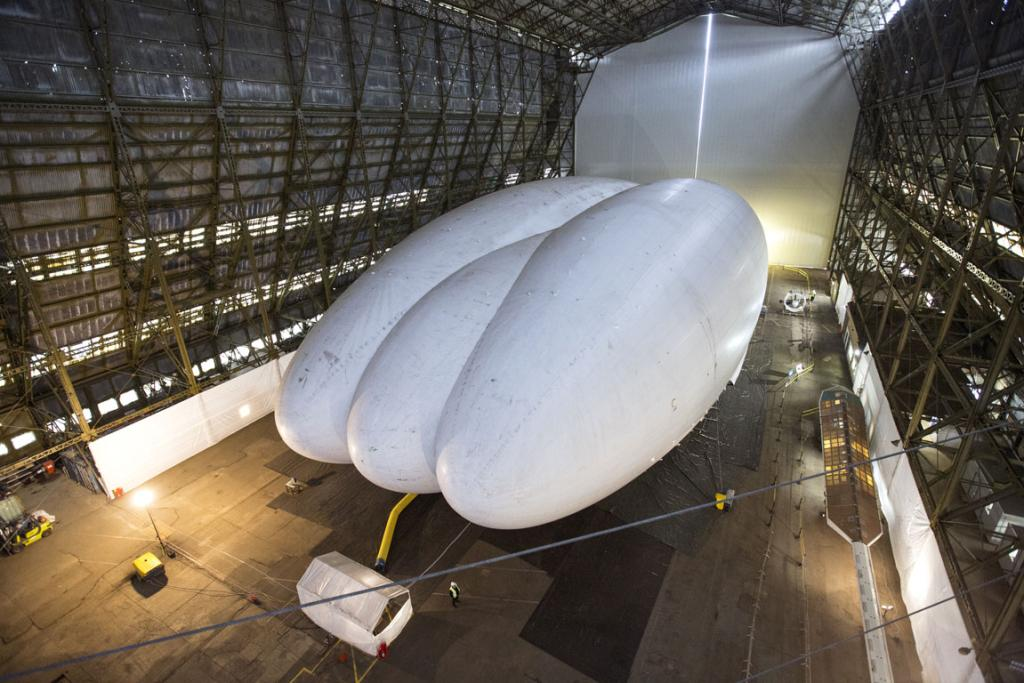 Mike Durham, the Technical Director at Hybrid Air Vehicles, admires the helium-filled 'Airlander' aircraft in a giant airship shed in Cardington, England. The tri-hull version is designed to carry passengers or cargo.