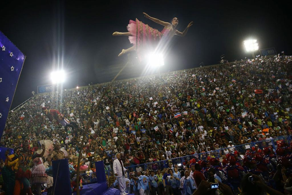 CARNIVAL: A member of the Uniao da Ilha samba school mounted on a flexible pole tips out over a crowd of thousands in Rio.