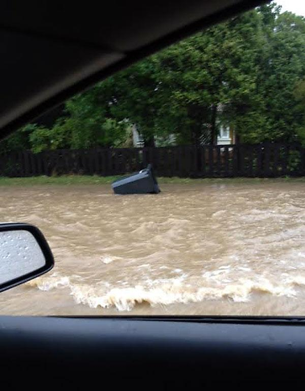 TIDAL: Floodwater washes a rubbish bin down the street in Little River.