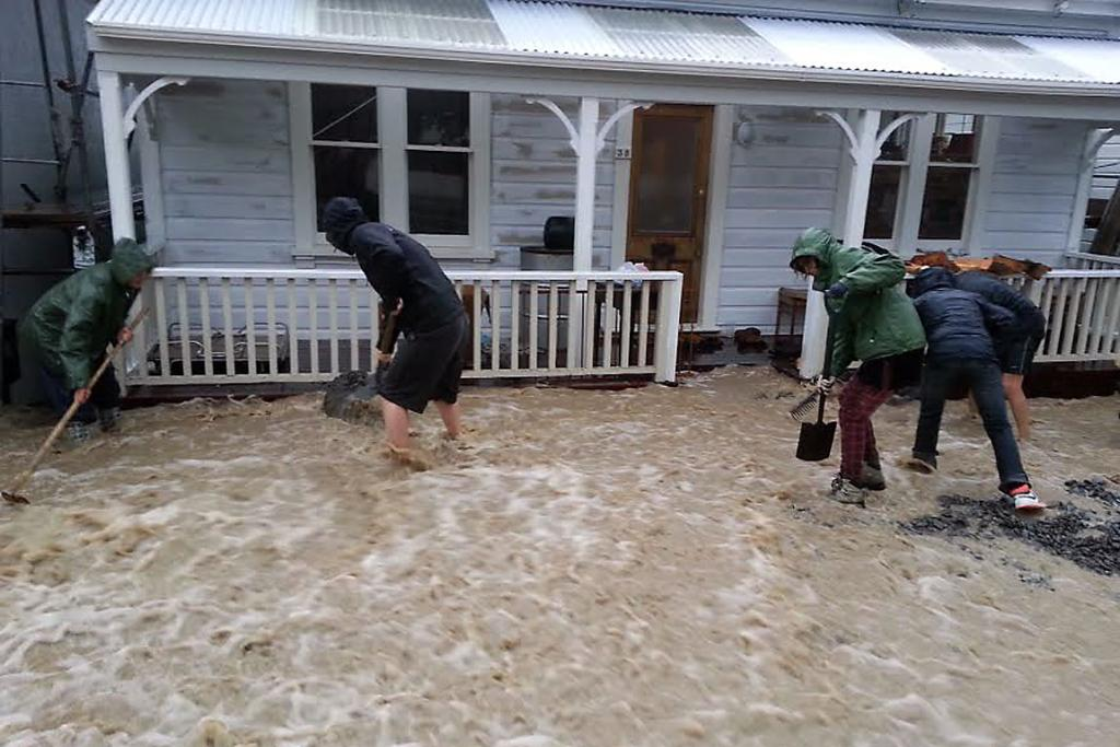 MAD RUSH: Residents shovel swiftly to save this Exeter St, Lyttelton, home from water damage.