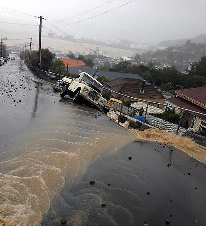 COLLAPSING: Floodwater and heavy winds push a truck over the street on Canterbury St, Lyttelton.