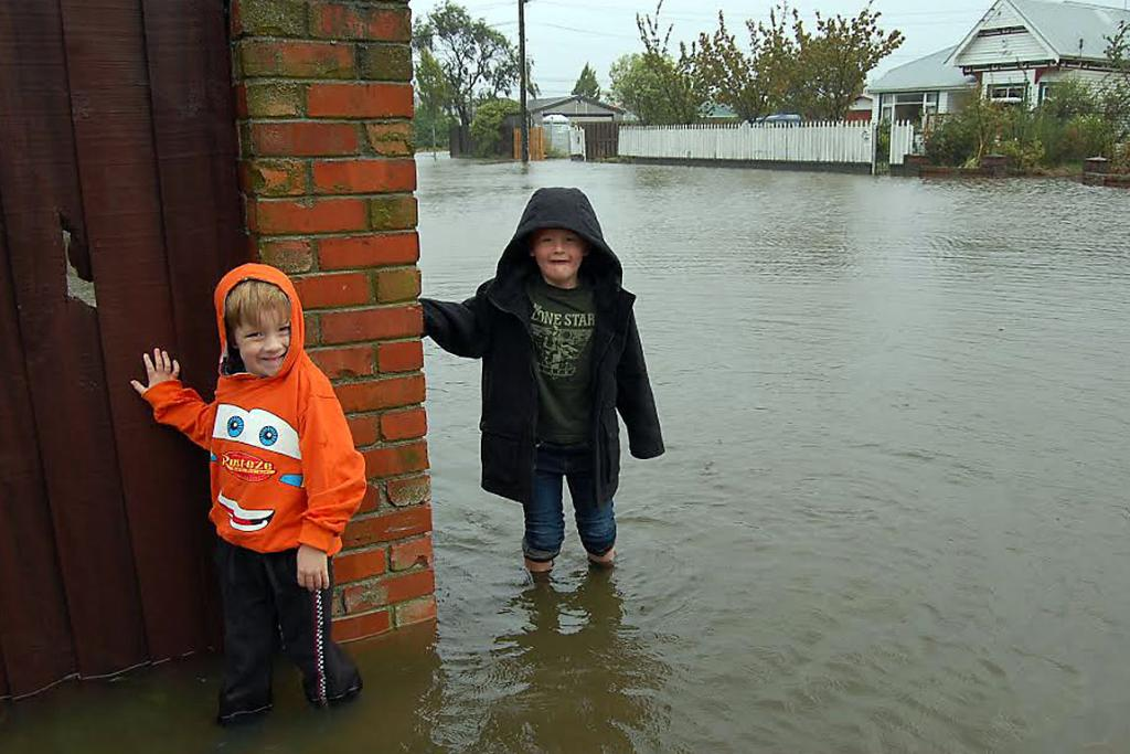 FINDING FUN IN THE FLOOD: Levi and Caleb White keep checking on the water levels in Wildberry St, Woolston.