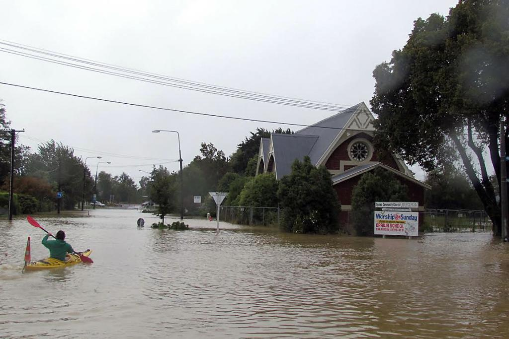 NAVIGATING FLOOD: A keen kayaker paddles towards the church on the corner of Aynsley Tce and Opawa Rd.
