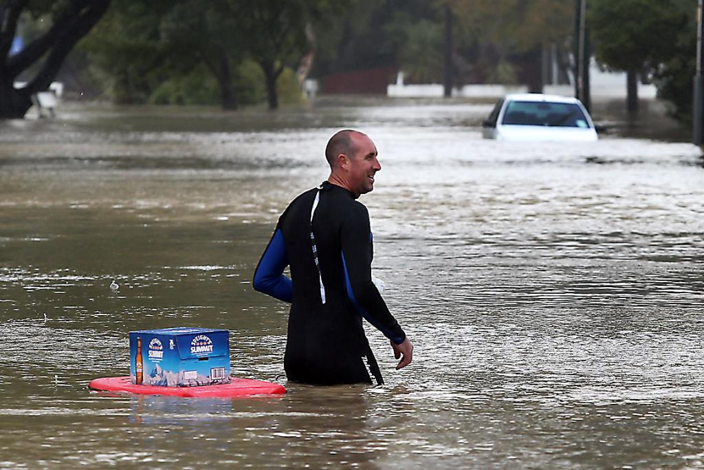 "IMPORTANT STUFF: A Riverlaw Terrace resident transports ""vital"" supplies on a body board through Heathcote River flood waters."