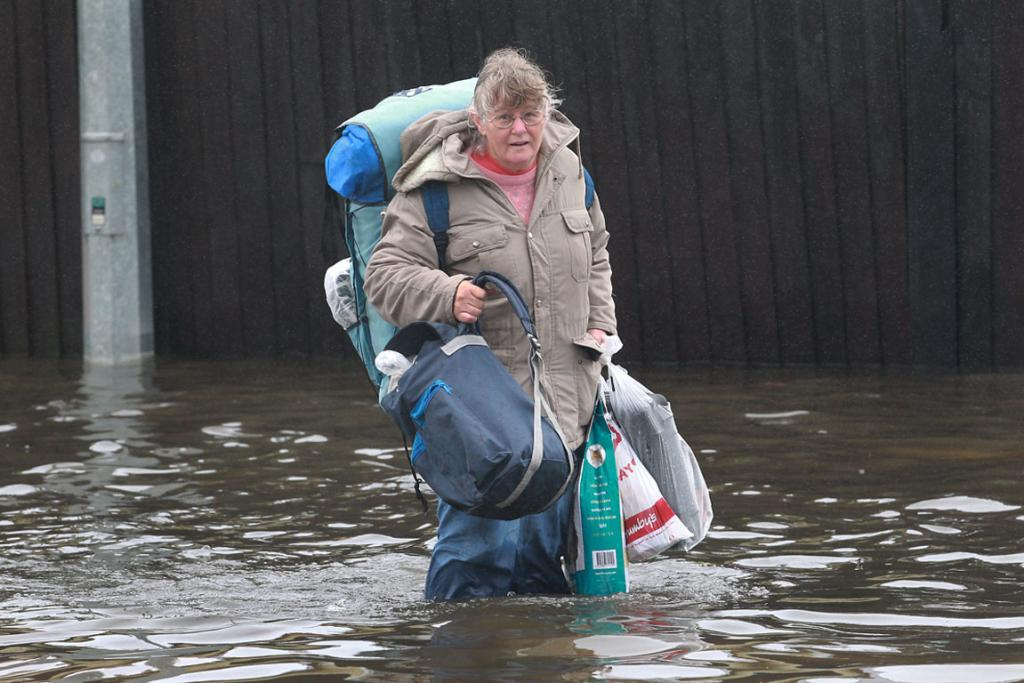 A months rain in 24 hours is how its been described. The city was grid locked in places for hours as commuters tried to get to work. Several St Alban's residents were evacuated and spent the night in a CD Welfare Centre The Avon River burst its banks. A woman carries her shopping through the flood waters.