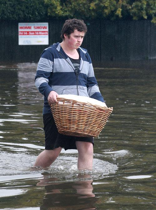 St Albans area. Sean Hermanspahn (17) wades through the water with his laundry.