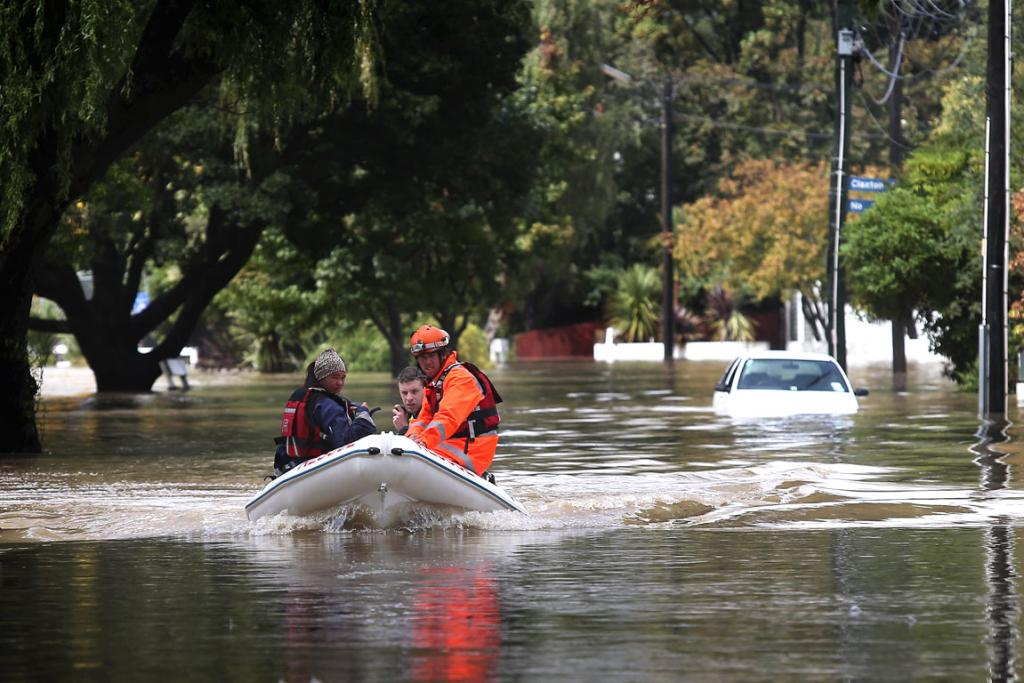Krystal Merrick and Dan Evans from the NZRT-12 Emergency Response/Rescue Team travel up the Heathcote River flooding waters along Riverlaw Terrace in their new rescue boat, donated from the lotteries ministry travel with a Red Cross member from RC23 team.